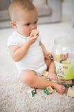 Śliczny mały dziecko siedzi na dywanie z zabawkami fotografia stock