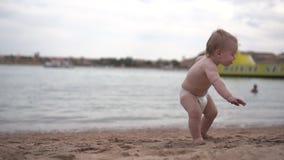 Śliczny mały dziecko siedzi na piasku na plaży odkrywa ten świat zbiory