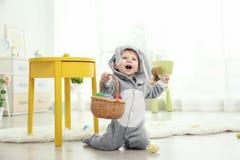 Śliczny mały dziecko w królika kostiumu bawić się z Wielkanocnymi jajkami Fotografia Royalty Free
