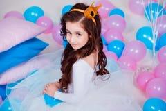Śliczny mały princess dziewczyny obsiadanie wśród balonów w pokoju nad białym tłem patrzeć kamerę Dzieciństwo Zdjęcia Royalty Free