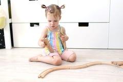 Śliczny mały 2 roku dziewczyny bawić się zabawkarską drewnianą linię kolejową fotografia stock