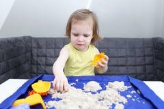 Śliczny mały 2 roku dziewczyny z kinetycznym piaskiem zdjęcie royalty free