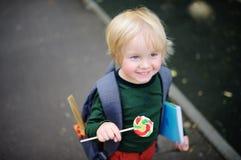Śliczny mały uczeń z jego lizakiem i plecakiem tylna koncepcji do szkoły Fotografia Stock