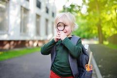 Śliczny mały uczeń z powiększać - szkło outdoors na słonecznym dniu tylna koncepcji do szkoły Obrazy Royalty Free