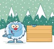 Śliczny Mały yeti kreskówki maskotki charakter Wskazuje Drewniany puste miejsce znak Zdjęcie Royalty Free