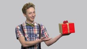 Śliczny nastoletni chłopak przedstawia prezenta pudełko zbiory