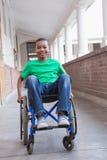 Śliczny niepełnosprawny uczeń ono uśmiecha się przy kamerą w sala fotografia stock
