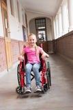 Śliczny niepełnosprawny uczeń ono uśmiecha się przy kamerą w sala obrazy stock