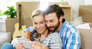 Śliczny pary obsiadanie przeciw kartonowi bierze selfie zbiory