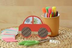 Śliczny podstępny ręcznie robiony czerwony samochód dla dzieciaków z kolorowymi pastelami i nożycami zdjęcia stock