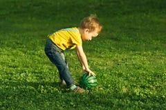 Śliczny pozytywny dzieciak, bawić się szczęśliwie z piłką na zielonej łące obrazy stock