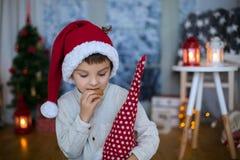 Śliczny preschool dziecko, chłopiec czyta książkę i je ciastka przy, Zdjęcie Stock