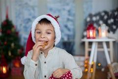 Śliczny preschool dziecko, chłopiec czyta książkę i je ciastka przy, Fotografia Stock