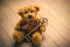 Śliczny puszysty miś z złotym kluczem na cudownym brązie wo Zdjęcia Royalty Free