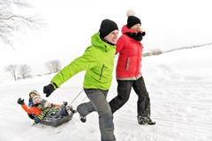 Śliczny Rodzinny ciągnięcie saneczki Przez Śnieżnego krajobrazu fotografia royalty free