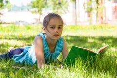 Śliczny rozważny małej dziewczynki lying on the beach na zielonej trawie w lata mienia i parka otwartej książce w ona ręki Obrazy Royalty Free