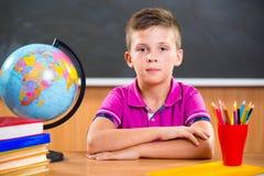 Śliczny skrzętny chłopiec obsiadanie w sala lekcyjnej Fotografia Stock