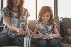 Śliczny skupiający się dzieciaka rysunek coś z jej mamą w domu fotografia stock