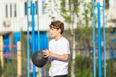 Śliczny sporty nastoletni chłopak bawić się koszykówkę outdoors przygotowywa dla strzelać Aktywny styl życia, fotografia stock