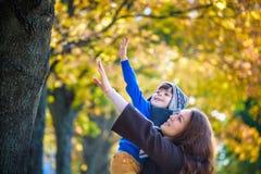 Śliczny, szczęśliwy, chłopiec, ono uśmiecha się i ściska z jego mamą wśród żółtych liści, Małe dziecko ma zabawę z matką w jesień zdjęcie royalty free