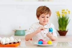 Śliczny szczęśliwy dzieciak, chłopiec maluje Easter jajka przy kuchennym biurkiem Obrazy Royalty Free