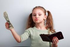Śliczny szczęśliwy dzieciak dziewczyny mienia portfel, dolary i myśl jak może zdjęcie stock