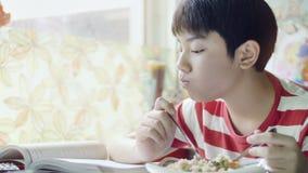Śliczny Tajlandzki chłopiec łasowanie smażył ryżowego jedzenie na białym stole w żywym pokoju zbiory