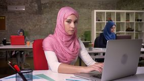 Śliczny uśmiech arabski kobiety n menchii hijab używa jej laptop i spogląda przy kamerą podczas gdy siedzący z innymi dziewczynam