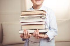 Śliczny uśmiechnięty chłopiec mienia stos książki Fotografia Royalty Free