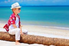 Śliczny uśmiechnięty chłopiec obsiadanie na palmowym drewnie przy piaskowatą plażą Zdjęcia Royalty Free