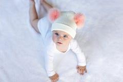 Śliczny uroczy dziecka dziecko z ciepłym białym i różowym kapeluszem z ślicznym bobbles Szczęśliwy dziewczynka uczenie kraul i pa obrazy royalty free