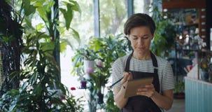 Śliczny właściciel biznesu pisze puszkowi ewidencyjnym działaniu w kwiatu sklepie samotnie zbiory