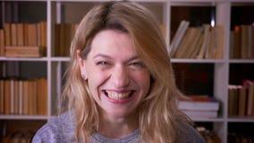 Śliczny w średnim wieku blondynka nauczyciel śmia się w kamerę jest niezwykle szczęśliwy przy biblioteką zbiory wideo