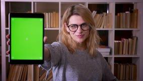 ?liczny w ?rednim wieku blondynka nauczyciel demonstrowa? joyfully zielonego chroma ekran pastylka w kamer? przy bibliotek? zdjęcie wideo