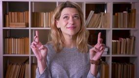 Śliczny w średnim wieku blondynka nauczyciel ono modli się z krzyżującymi palcami pokazywać nadzieję w kamerę przy biblioteką zdjęcie wideo