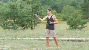 Śliczny wysoki mężczyzna wszczyna quadrocopter w drewnach i trzyma trutnia lub zbiory