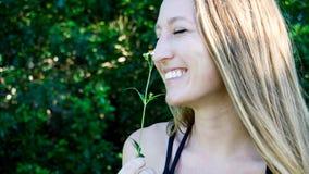 Śliczny zamknięty portret młoda blondynki kobiety twarz uśmiecha się śmiać się z zamkniętymi oczami i stokrotka kwiatem odizolowy zdjęcie stock