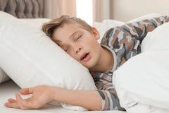 Śliczny zmęczony chłopiec dosypianie w łóżku zdjęcie royalty free