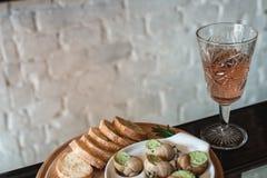 Ślimaczki z ziele masłem w tradycyjnym ceramicznym niecka chlebie na drewnianej desce, szkło wina fotografia stock