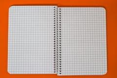 Ślimakowaty notatnik przy pomarańczowym tłem Zdjęcie Royalty Free