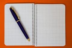 Ślimakowaty notatnik z błękitnym piórem Obraz Stock