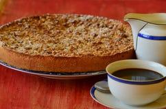 Śliwka rozdrobni tarta z filiżanką kawy i creamerem na czerwonym tle obraz stock