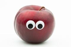 Śliwka z googly oczami na białym tle Obrazy Royalty Free