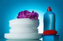 Ślizga się czystych naczynia, detergent i gąbki, kwiaty Storczykowi na błękicie fotografia royalty free