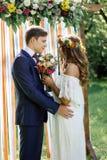 Ślubna ceremonia przy plenerowym parkiem - państwo młodzi dotyka each inny Fotografia Royalty Free