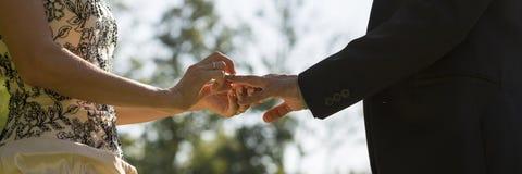 Ślubna ceremonia - zbliżenia panna młoda umieszcza pierścionek na ona widok Zdjęcie Royalty Free