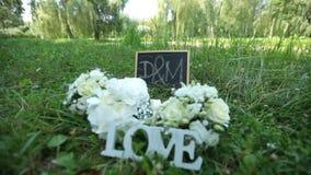 Ślubna dekoraci słowa miłość, kwiaty i drewniana plakieta z listów d M na tle zielona trawa w i zbiory