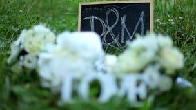 Ślubna dekoraci słowa miłość, kwiaty i drewniana plakieta z listów d M na tle zielona trawa w i zbiory wideo
