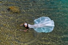 Ślubna kobieta lub panna młoda w biel sukni w wodzie morskiej Obrazy Stock