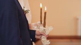 Ślubne świeczki w rękach państwo młodzi w kościół zdjęcie wideo
